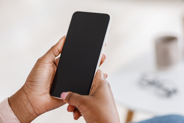 Mockup of smartphone with black screen in hands of unrecognizable black woman