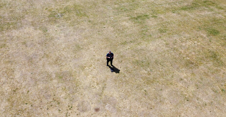 A photograph of the photographer taken with the drone he is controlling in a green sun dried field.