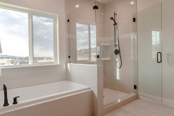 Built in bathtub with black faucet and shower stall with half glass enclosure