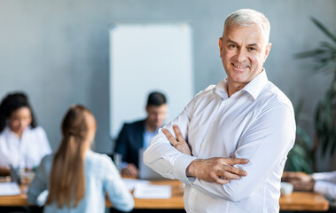 Businessman Standing Crossing Hands In Front Of Employees In Office