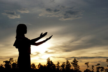 silhouette of a woman asking for blessings from God Evening sun background