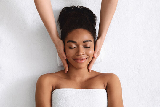 Top view of relaxed black woman having facial massage