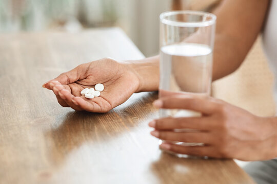 Dietary Supplements. Unrecognizable Black Woman Taking Pills And Drinking Water At Home