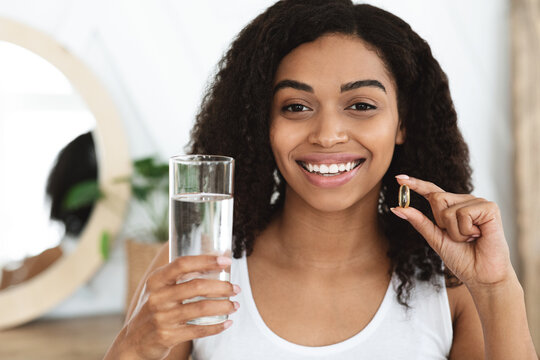 Vitamins And Food Supplements. Smiling Black Woman Holding Omega-3 Capsule And Water
