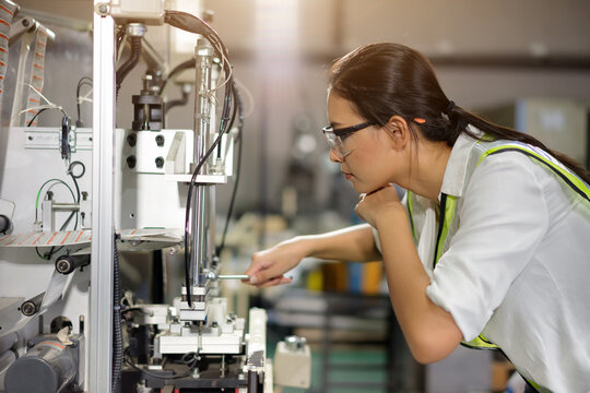Young female engineer is setting automation machine in work shop.