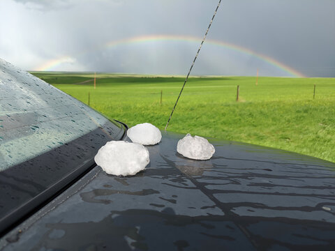 Giant hailstones displayed on a black car after a powerful storm has passed. A rainbow can be seen in the background.