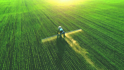 Canvas Prints Culture Tractor spray fertilizer on green field drone high angle view, agriculture background concept.