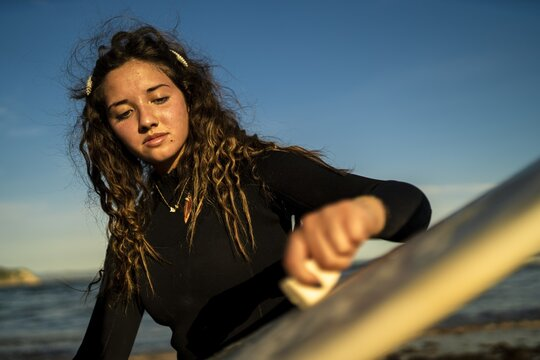 Selective focus shot of an attractive female waxing her surfboard at the beach in Spain