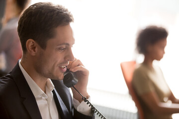 Confident businessman employee talking on landline phone in office close up, discussing project or...