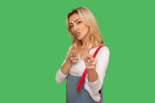 Hey, I'll kill you! Portrait of adult woman in denim overalls pointing finger pistols to camera, pretending to shoot, threatening with hand gun gesture. indoor studio shot isolated on green background