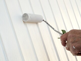 Mann streicht Garagentor in Weiß