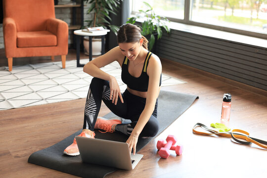 Beautiful slim sporty woman in sportswear is sitting on the floor with dumbbells and bottle of water and is using a laptop at home in the living room. Healthy lifestyle. Stay at home activities.