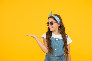 retro girl presenting product. small kid wear summer outfit. cheerful child has vintage look. headkerchief and sunglasses - summer accessory. beauty and fashion. happy childhood. copy space