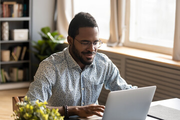 African millennial guy sit at desk at home or cozy modern office room look at laptop screen do...