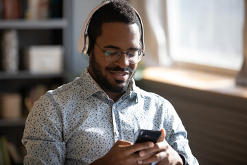 African man wear headphones holds cellphone choose track listens digital music or podcast, using video streaming service. Language learning platform most downloaded education app advertisement concept