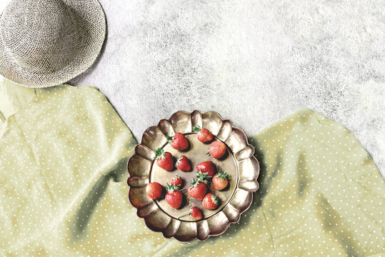 Retro summer theme with polka dot green dress, straw hat and strawberry in vintage brass dish.