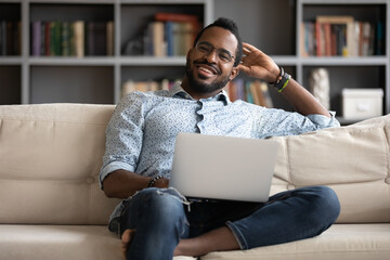 Smiling millennial African guy sit on couch in living room working on wireless pc from home, happy young man resting on sofa browsing internet shopping using computer, modern technology usage concept