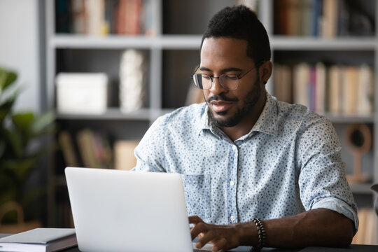 Busy african man freelancer using modern professional app do remote work seated at desk homeoffice cozy room. Employee working typing business e-mail. E-business, e-learning, e-commerce user concept