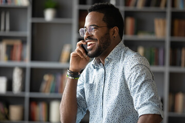 African ethnicity 35s businessman holding mobile phone enjoy conversation with client or personal...