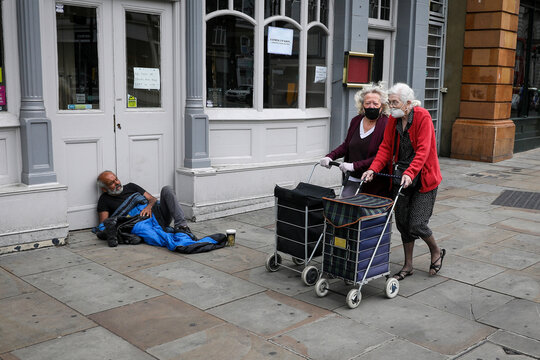 Women wearing face masks and pushing shopping bags on wheels walk past a homeless man in London
