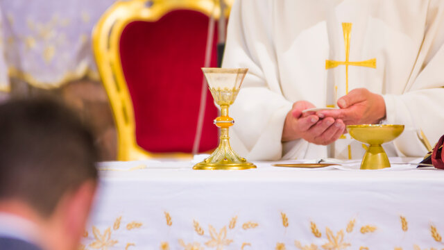 hands of Pope Francis with host and chalice with wine in the churches of the world
