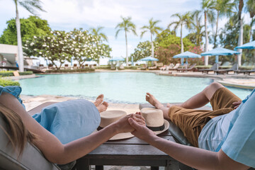 Young couple traveler enjoying a summer vacation at swimming pool in tropical resort near the...