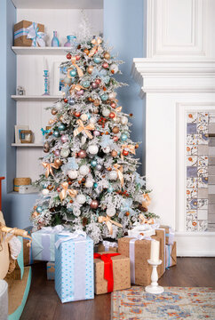 Christmas decorated fir tree in a room with a fireplace,  light blue room, interior