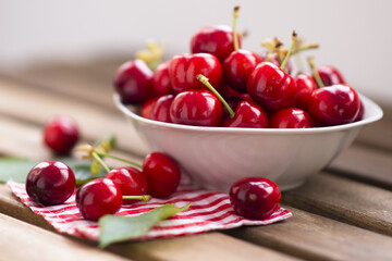 fresh cherries fruits in a white bowl on wooden table