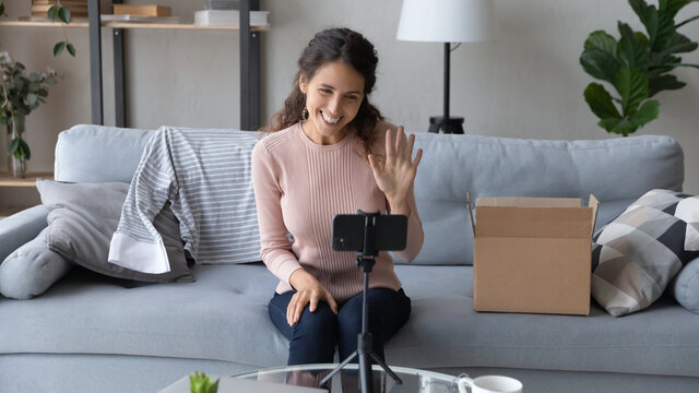 Smiling young woman blogger shooting beauty vlog on smartphone, waving hand at camera, greeting subscribers, beautiful girl sitting on couch at home, recording unpacking clothing review video