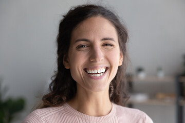 Head shot portrait close up laughing overjoyed beautiful woman with toothy smile looking at camera, making video call to friends or relatives, excited young female blogger recording vlog