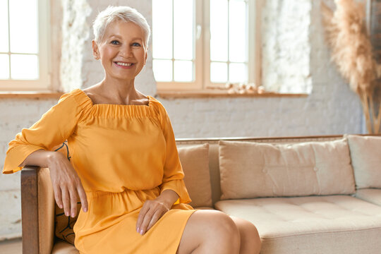 People, lifestyle, leisure, retirement and relaxation. Indoor shot of beautiful fashionable European female pensioner in yellow dress sitting comfortably on couch in living room, smiling happily