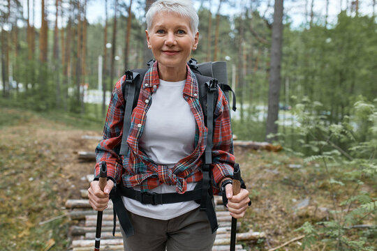 Outdoor activities, people and vacations concept. Attractive short haired middle aged woman in activewear hiking in forest using poles for nordic walking, doing aerobic workout, enjoying nature