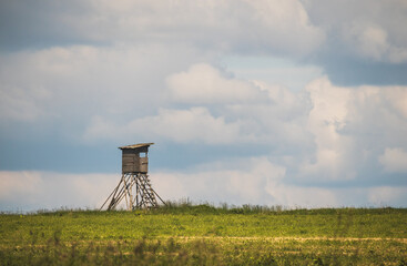 hunting blind on a field, in the background the sky with white clouds