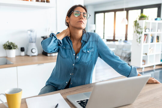Tired business woman with neck pain looking uncomfortable while working from home on laptop.