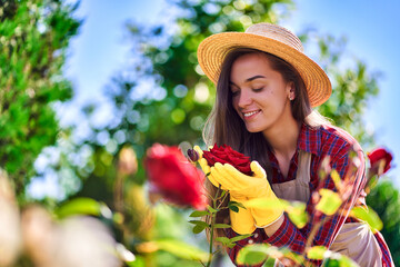 Attractive happy smiling woman gardener in straw hat, apron and yellow rubber gloves smells and...