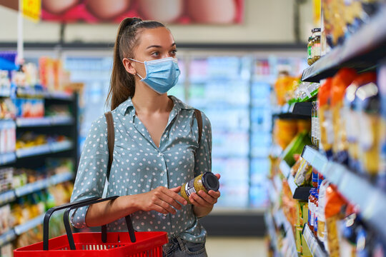 Young woman buyer wearing medical protective mask among the shopping shelves chooses food products in a grocery store