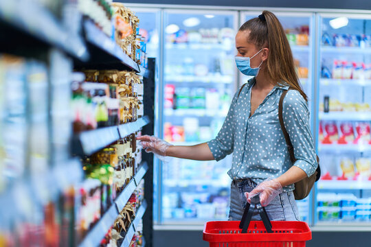 Young woman buyer in a protective face mask and transparent gloves with shopping basket chooses products in a grocery shop
