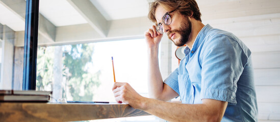 Handsome man with stubble and eyeglass working at home near big bright window in his own house. Remote workplace. Thinking with pencil in hand. Wide screen panoramic