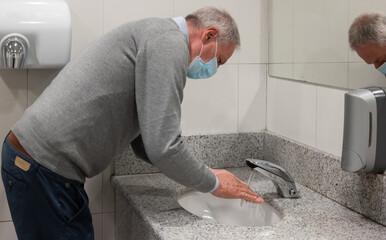 Senior man washing his hands in a public restroom