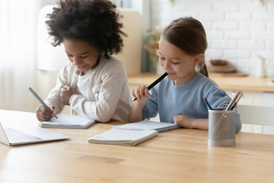 Two multiethnic sisters little girls doing homework sit in kitchen at home. Holding felt-tip pens writing essay on workbook, thinking on common task. Homeschooling, education, learning process concept