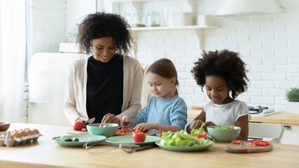Happy motherhood, healthy good eating, mom teach small biracial multiracial kids cooking activity...