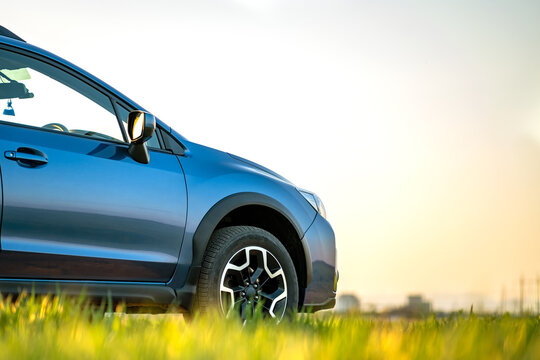 Close up of blue off road car on green grass. Traveling by auto, adventure in wildlife, expedition or extreme travel on a SUV automobile. Offroad 4x4 vehicle in field at sunrise.