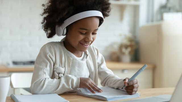 African schoolgirl sit at table writing in workbook studying distantly using laptop app, wears headphone listen educational audio. Self-education, quarantine and learn from home, homeschooling concept