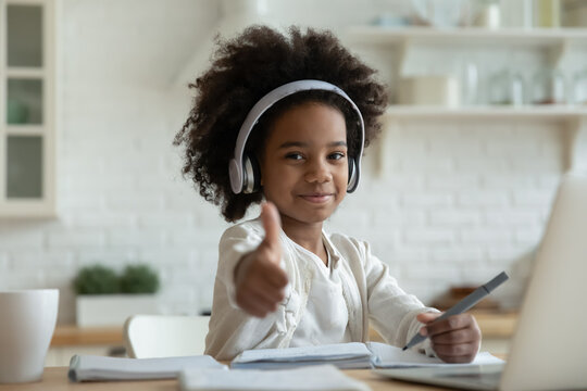 African girl in headphones enjoy e-learn sit at table showing thumbs up recommend e-study easy and interesting app for children, using modern tech. Homeschooling, clever kid and self-education concept