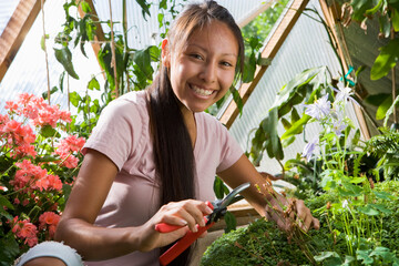 Hispanic mother and teen daughter gardening in geodesic dome