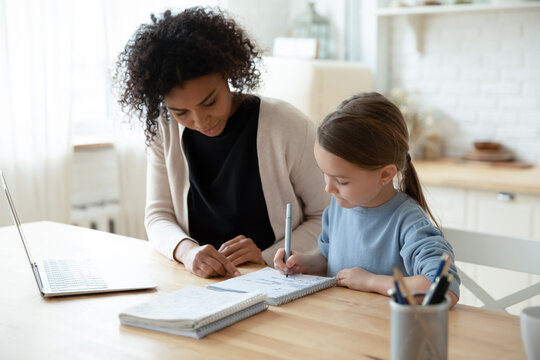 Home schooling conducted by parent or home tutor during quarantine time concept. African caring stepmom or nanny helps with school subject little daughter adorable kid girl, seated at table in kitchen