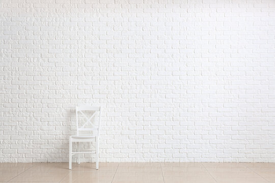 Chair near white brick wall in room