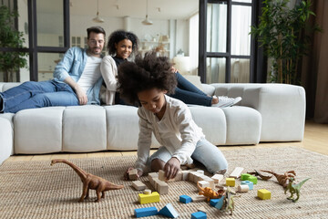 African daughter play on floor with wooden blocks set and dinosaur toys while multi ethnic parents...