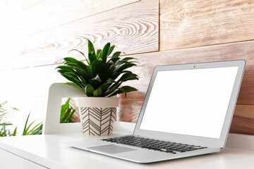 Comfortable workplace with modern laptop and houseplant near wooden wall