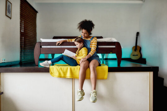 Make friends with a book. African american baby sitter and caucasian little girl reading book, fairy tale together while sitting at home. Children education, leisure activities, babysitting concept